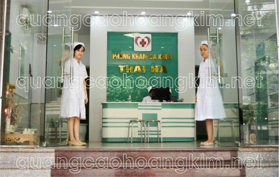 backdrop quầy lễ tân phòng khám gắn logo và chữ inox vàng gương